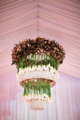 custom tiered floral chandelier made of gilded leaves, fringe, and upside-down creamy calla lilies