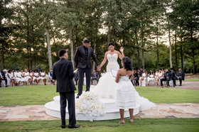 Bride and groom on raised platform outdoor courtyard private estate wedding ceremony white flowers