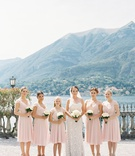 bride in pretty wedding dress with flower girl and bridesmaids in short knee length pink dresses