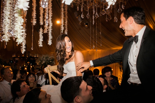 Bride and groom look at each other during hora dance wedding reception flower chandelier