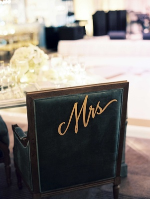 Black chair at sweetheart table with Mrs sign dangling from back in modern cursive calligraphy