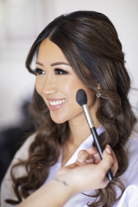 bride with hair down curls natural makeup pretty eyelashes makeup artist with blush brush
