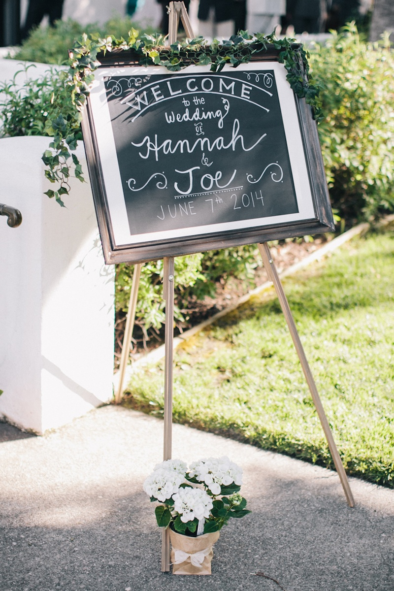 Vineyard wedding chalkboard welcome signs topped by greenery