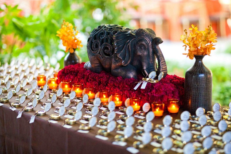 Wedding place card table decorated with an elephant on a bed of red flowers surrounded by candles
