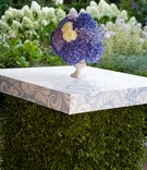 a small floral arrangement made up of blue purple white flowers on hard top stand greenery bottom