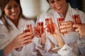 bridesmaid in white robes with tall champagne flutes and raspberry fruits