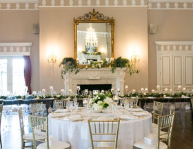 Wedding reception fireplace gold mirror greenery white table wood reception table head table candles