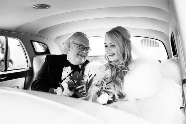black and white photo of bride and her father on their way to the ceremony
