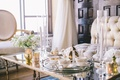 Wedding reception with white and gold coffee servide on a mirror-top table with golden candleholders