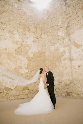 Bride in strapless Romona Keveza wedding dress kissing groom at mission