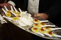 Tray-passed banana creme brulee on white spoons