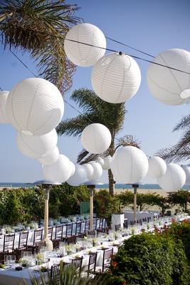 White sphere paper lanterns above beach wedding