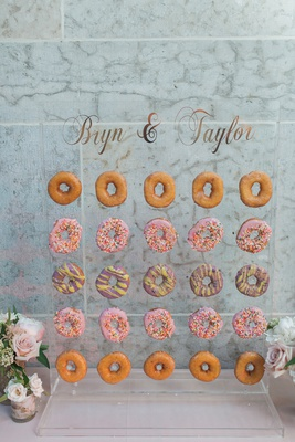 colorful donut wall on acrylic stand at wedding reception