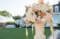 Cream urn at outdoor ceremony with white hydrangea, white and pink roses flowers, amaranthus