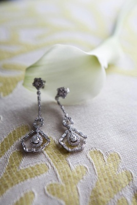 Vintage-inspired diamond bridal earrings on textile