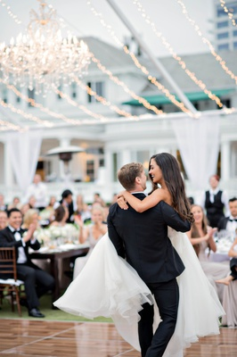 groom lifts bride in the air during first dance, bride in reem acra wedding dress with her hair down