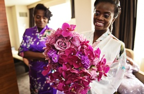 Bride in robe holds bouquet of magenta orchids, light purple roses