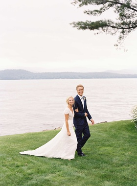 Bride in Carolina Herrera short sleeve lace wedding dress with groom in navy tuxedo by lake house