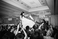 black and white photo of bride and groom lifted in chairs jewish reception tradition