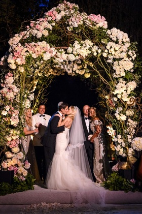 Bride and groom kissing under floral chuppah