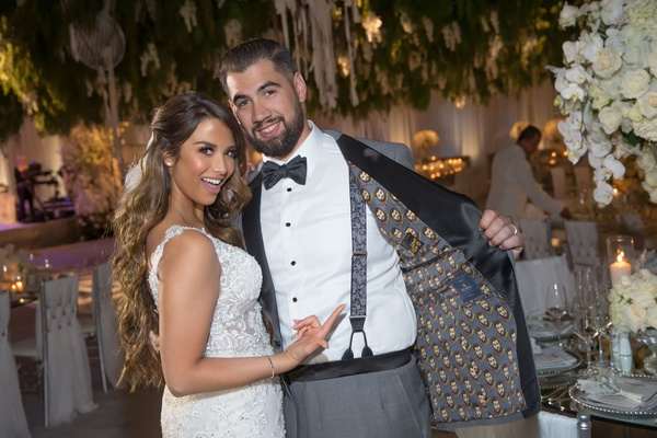groom wearing custom tuxedo jacket with his face on the inside lining suspenders and bow tie