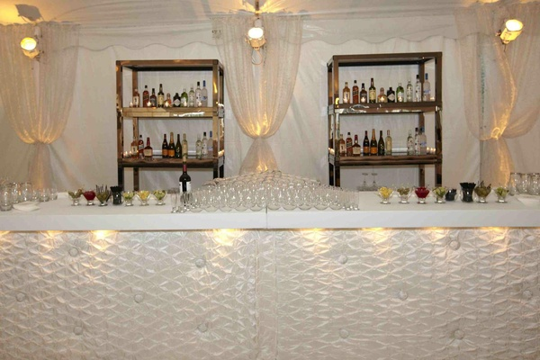 Bar area with tufted fabric bar and white drapery