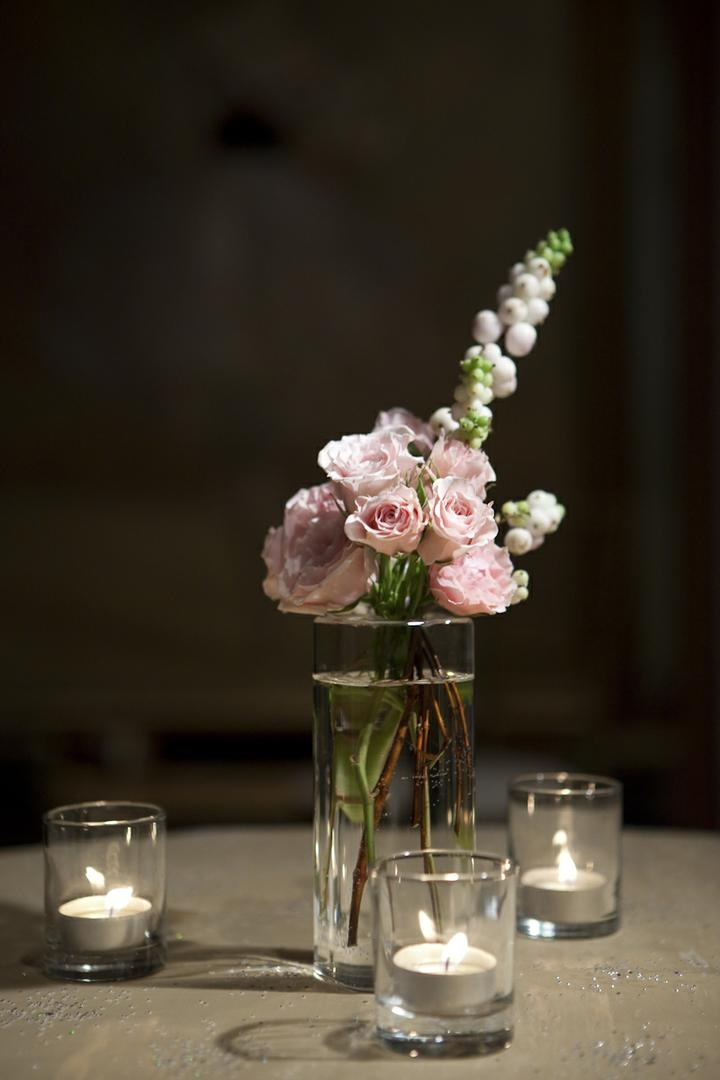 Tea lights surrounding small vase with ranunculus
