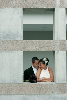 Bride and groom looking at each other in cement window