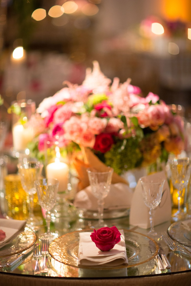 Wedding reception decoration mirror table glass charger with gold rim pink red rose on top of napkin