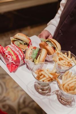 Wedding reception french fries in glass cups with double double burgers on tray wedding late night