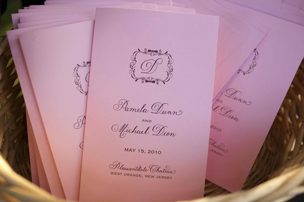 Pink wedding programs with the couple's monogram