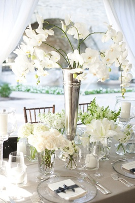 white flowers with green leaves foliage on table with gray table linens and glass plates and glasses