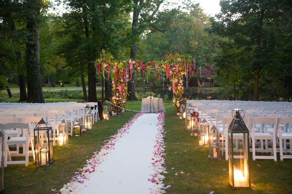 Jewish wedding ceremony outdoors grass white aisle runner flower petals greenery chuppah with pink