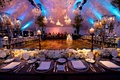 Tented reception with crystal chandeliers over dance floor, blue lighting, tan damask projections