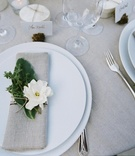 Wedding reception place setting with flax napkin and herbs and gardenia