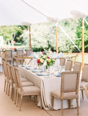 Tent wedding reception beige wood furniture around table light blue linen napkins flowers colorful