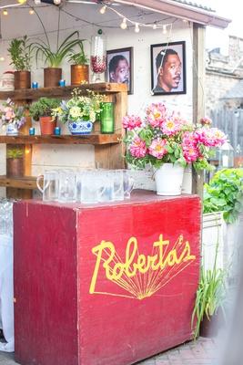 roberta's rehearsal dinner, portraits of Eddie Murphy, pink flowers