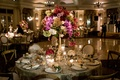 Ballroom reception with gold linen tall centerpiece purple and burgundy flowers gold chairs roses
