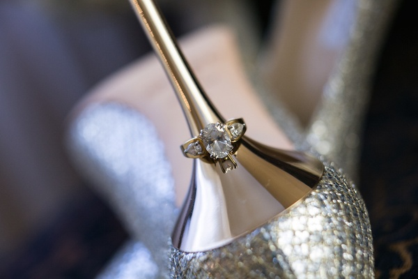 Engagement ring with round center diamond, pear side diamonds on Jimmy Choo gold heel
