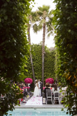 Bride and groom in between palm trees at hotel pool wedding
