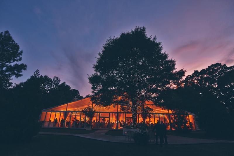 Illuminated backyard tent and trees at sunset