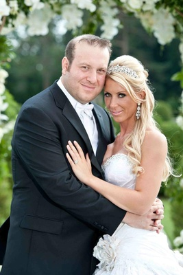 Bride in a strapless Pnina Tornai gown with groom in a black tuxedo and white bow tie and vest