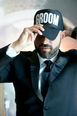 Groom putting on groom baseball cap trucker hat white lettering black hat