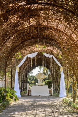 White wedding table under arch of vines and greenery