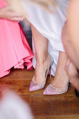 bride puts on christian louboutin pointed toe clear heels with rhinestone embellishments