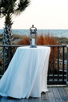 White cocktail table with wooden lantern next to ocean