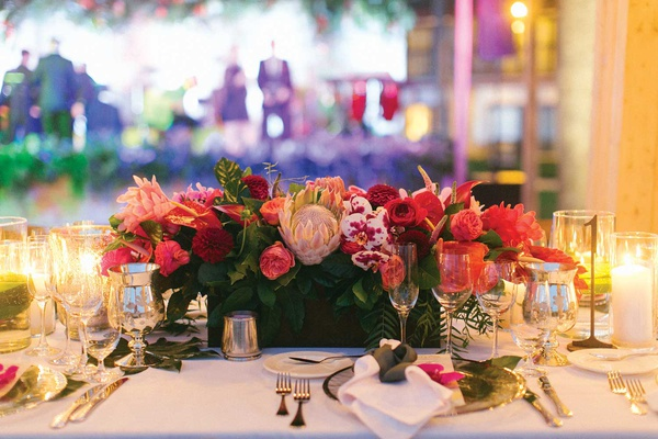 wedding reception low centerpiece box with pink red fuchsia flowers rose protea orchid leaves candle