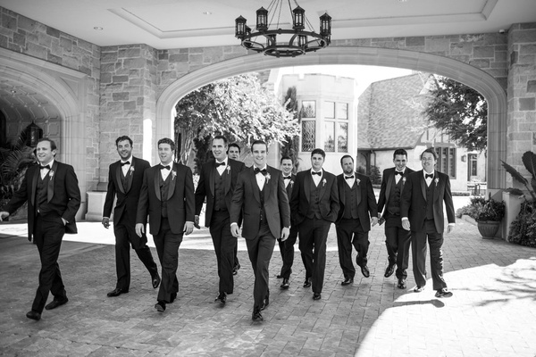Black and white photo of groom and groomsmen black and white look fancy and walk together