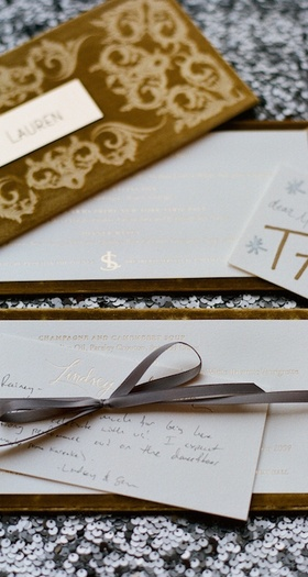 Gold velvet box on sequin tablecloth with handwritten note to guests