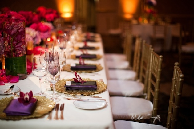 White tables topped with gold charger plates
